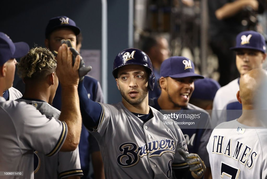 Ryan Braun #8 of the Milwaukee Brewers celebrates in the dugout with teammates after scoring to tie the game in the eighth inning of the MLB game against the Los Angeles Dodgers at Dodger Stadium on August 1, 2018 in Los Angeles, California. The Dodgers defeated the Brewers 6-4 in ten innings.