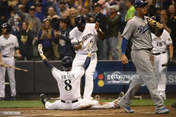 Ryan Braun of the Milwaukee Brewers celebrates with Lorenzo Cain after scoring a run off of a double hit by Jesus Aguilar of the Milwaukee Brewers...