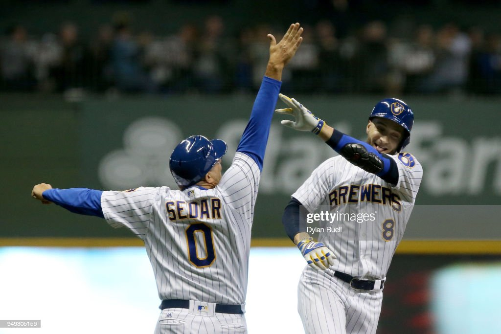 Ryan Braun #8 of the Milwaukee Brewers celebrates with third base coach Ed Sedar after hitting a home run in the fourth inning against the Miami Marlins at Miller Park on April 20, 2018 in Milwaukee, Wisconsin.