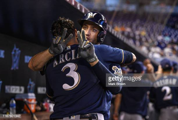 Ryan Braun of the Milwaukee Brewers gestures the number of Christian Yelich while celebrating with Orlando Arcia after hitting a two run homerun in...