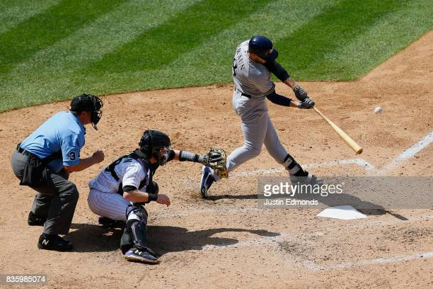 Ryan Braun of the Milwaukee Brewers hits an RBI sacrifice fly as catcher Ryan Hanigan of the Colorado Rockies and home plate umpire Sam Holbrook look...
