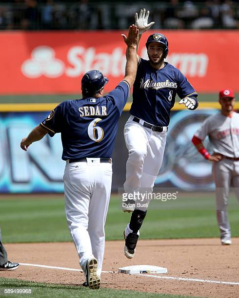 Ryan Braun of the Milwaukee Brewers is congratulated by third base coach Ed Sedar after hittin a home run in the second inning against the Cincinnati...
