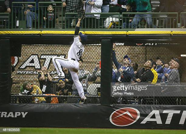 Ryan Braun of the Milwaukee Brewers leaps up on the wall as he watches the two run home run of Atlanta Braves' Jason Heyward in the fifth inning of a...