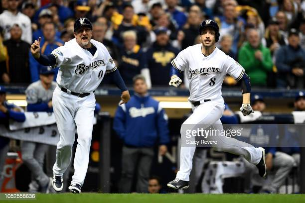 Ryan Braun of the Milwaukee Brewers scores a run off of a double hit by Jesus Aguilar of the Milwaukee Brewers during the first inning in Game Six of...