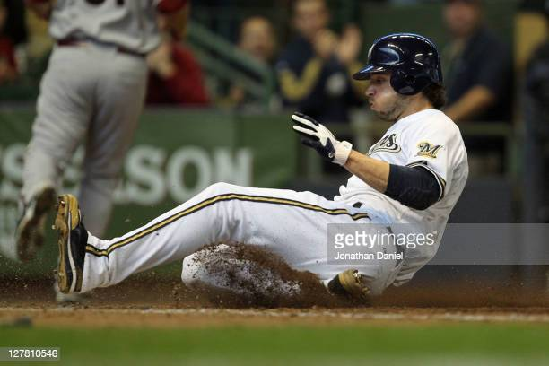 Ryan Braun of the Milwaukee Brewers scores on a sacrifice fly ball by Jerry Hairston Jr #15 in the fourth inning during Game One of the National...