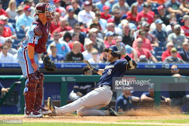 Ryan Braun of the Milwaukee Brewers scores on a sacrifice fly by Yasmani Grandal as catcher Andrew Knapp of the Philadelphia Phillies waits for the...