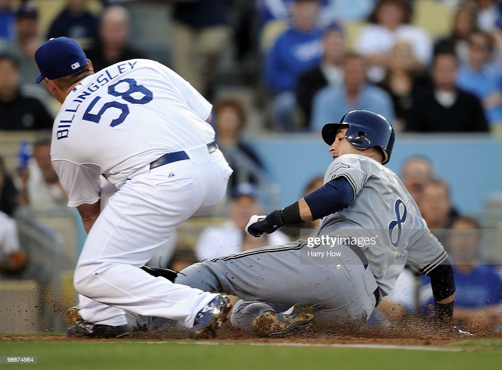 Ryan Braun #8 of the Milwaukee Brewers slides in for a run ahead of the tag by Chad Billingsley #58 of the Los Angeles Dodgers after a wild pitch for a 3-0 lead during the first inning at Dodger Stadium on May 5, 2010 in Los Angeles, California.