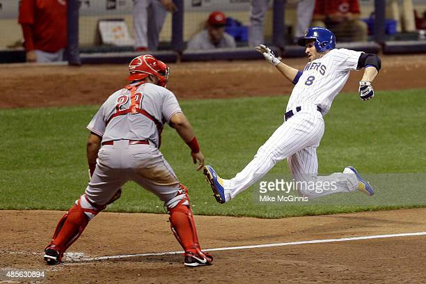 Ryan Braun of the Milwaukee Brewers slides into home plate on a 2 RBI double hit by Adam Lind in the eighth inning against the Cincinnati Reds at...
