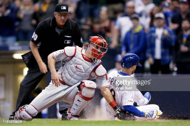 Ryan Braun of the Milwaukee Brewers slides into home plate to score a run past JT Realmuto of the Philadelphia Phillies in the first inning at Miller...