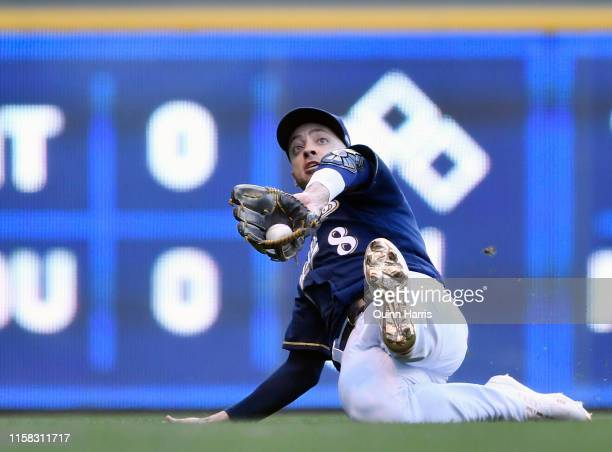 Ryan Braun of the Milwaukee Brewers slides to make the catch in the first inning against the Seattle Mariners at Miller Park on June 25 2019 in...