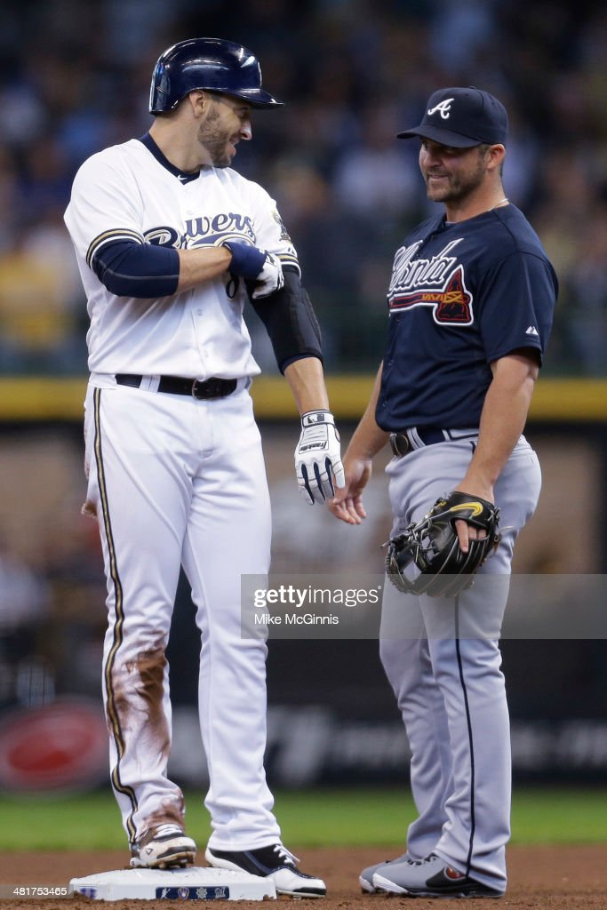 Ryan Braun #8 of the Milwaukee Brewers talks to Dan Uggla #26 of the Atlanta Braves after hitting a single in the bottom of the fourth inning against the Atlanta Braves during Opening Day at Miller Park on March 31, 2014 in Milwaukee, Wisconsin.