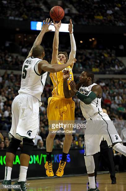 Ryan Broekhoff of the Valparaiso Crusaders is fouled by Branden Dawson of the Michigan State Spartans as he attempts a shot against Adreian Payne of...