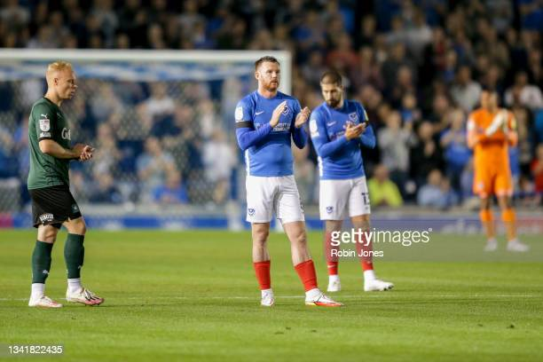 Ryan Broom of Plymouth Argyle and Ryan Tunnicliffe and Kieron Freeman of Portsmouth FC clap on the 10 minute mark in memory of Sophie Fairall, a...