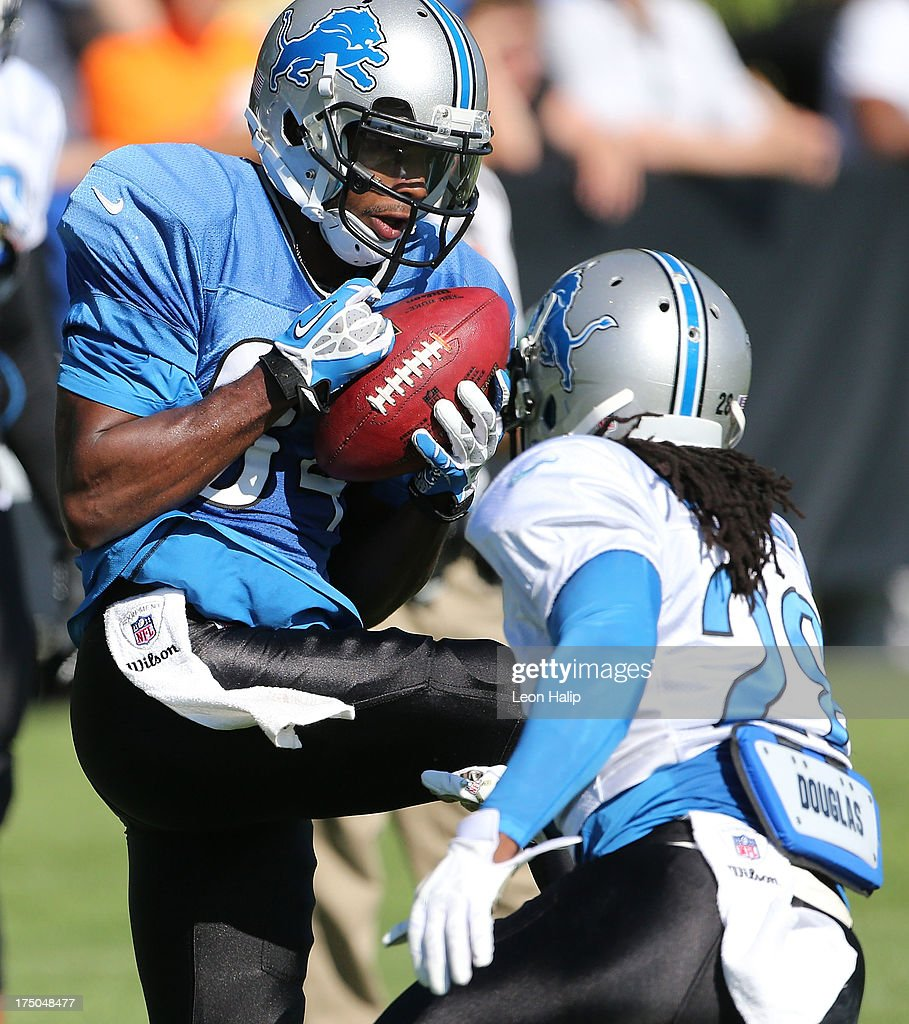 Ryan Broyles #84 and Bill Bentley #28 of the Detroit Lions battle for the ball during training camp on July 30, 2013 in Allen Park, Michigan.