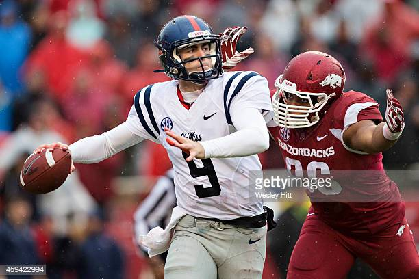 Ryan Buchanan of the Ole Miss Rebels throws a pass under pressure from Trey Flowers of the Arkansas Razorbacks in the second quarter at Razorback...