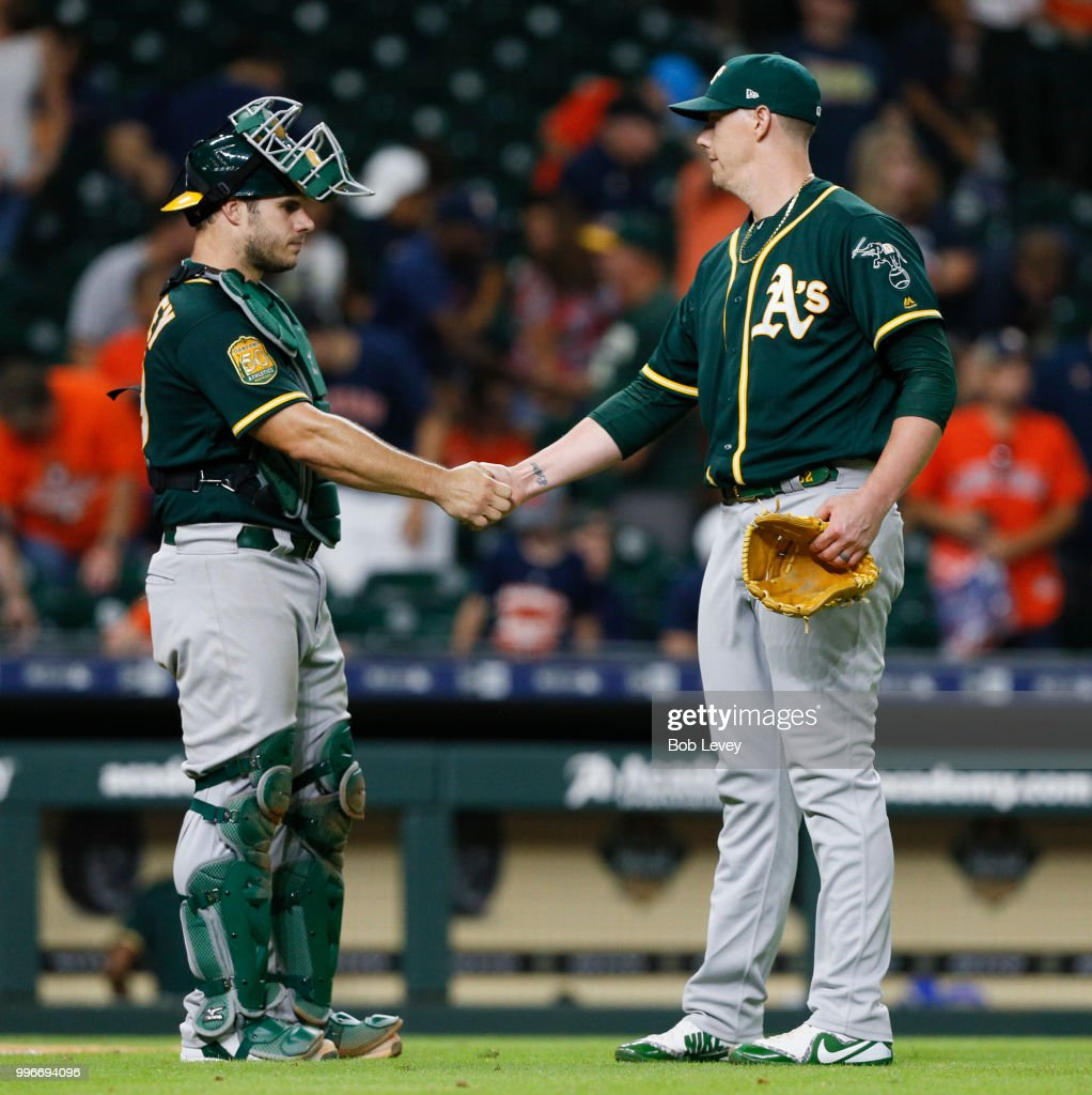 Ryan Buchter #52 of the Oakland Athletics shakes hands with catcher Josh Phegley #19 after the final out at Minute Maid Park on July 11, 2018 in Houston, Texas.