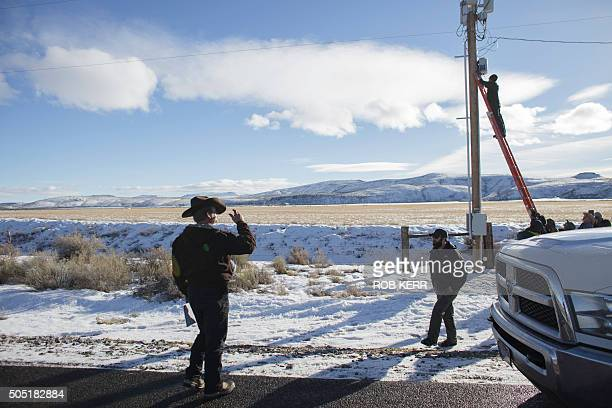 Ryan Bundy in cowboy hat observes as a member associated with his group of protestors disables a power pole remote camera location near the occupied...