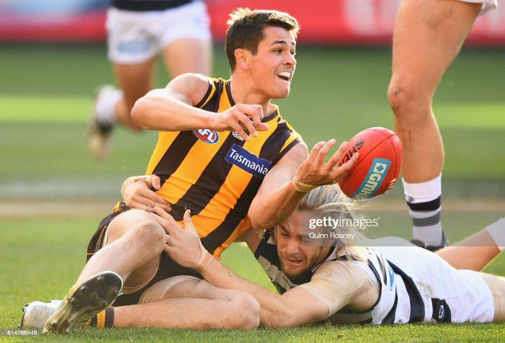 Ryan Burton of the Hawks handballs whilst being tackled by Cameron Guthrie of the Cats during the round 17 AFL match between the Geelong Cats and the Hawthorn Hawks at Melbourne Cricket Ground on July 15, 2017 in Melbourne, Australia.
