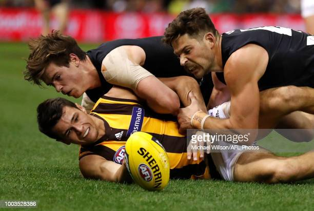 Ryan Burton of the Hawks is tackled by Paddy Dow of the Blues and Levi Casboult of the Blues during the 2018 AFL round 18 match between the Carlton...