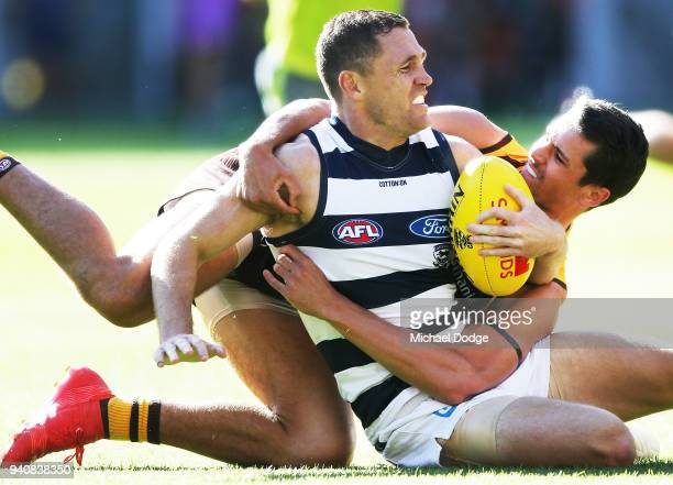 Ryan Burton of the Hawks tackles Joel Selwood of the Cats during the round two AFL match between the Geelong Cats and the Hawthorn Hawks at Melbourne...