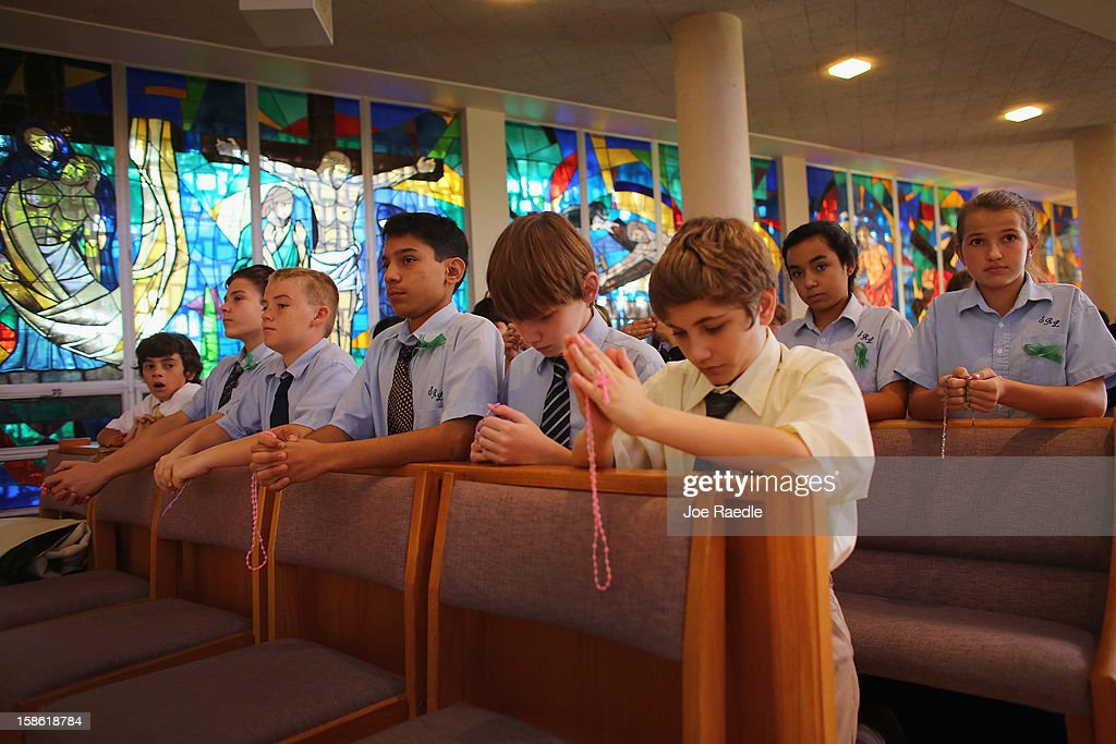 Ryan Caccamise, Warren Gammill, Tyler O'Connor, Joshua Toledo, Sean Fee and Thomas Balaki pray during a service, at St. Rose of Lima School, for the victims of the school shooting one week ago in Newtown, Connecticut on December 21, 2012 in Miami, Florida. Across the country people marked the one week point since the shooting at Sandy Hook Elementary School in Newtown, Connecticut that killed 26 people.
