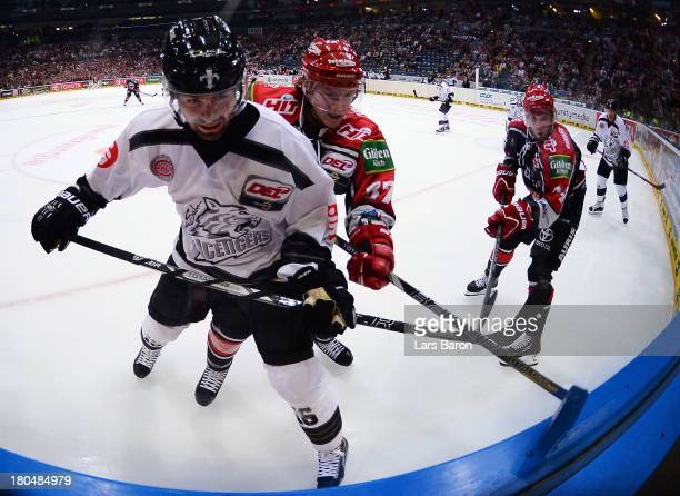 Ryan Caldwell of Ice Tigers is challenged by Marcel Ohmann of Koeln during the DEL match between Koelner Haie and Thomas Sabo Ice Tigers at Lanxess...
