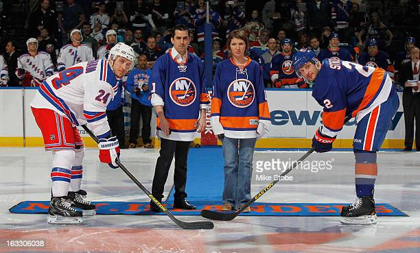 Ryan Callahan of the New York Rangers and Mark Streit of the New York Islanders come out for the ceremonial puck drop with Katie Beers and Cameron...