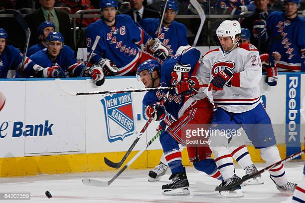 Ryan Callahan of the New York Rangers battles for a loose puck against Robert Lang of the Montreal Canadiens during the first period on January 7,...