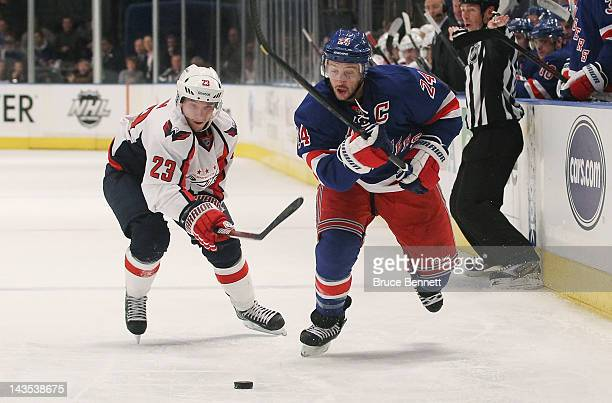 Ryan Callahan of the New York Rangers controls the puck against Keith Aucoin of the Washington Capitals in Game One of the Eastern Conference...