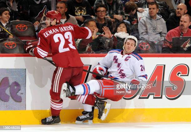 Ryan Callahan of the New York Rangers falls to the ice after being checked by Oliver EkmanLarsson of the Phoenix Coyotes at Jobingcom Arena on...