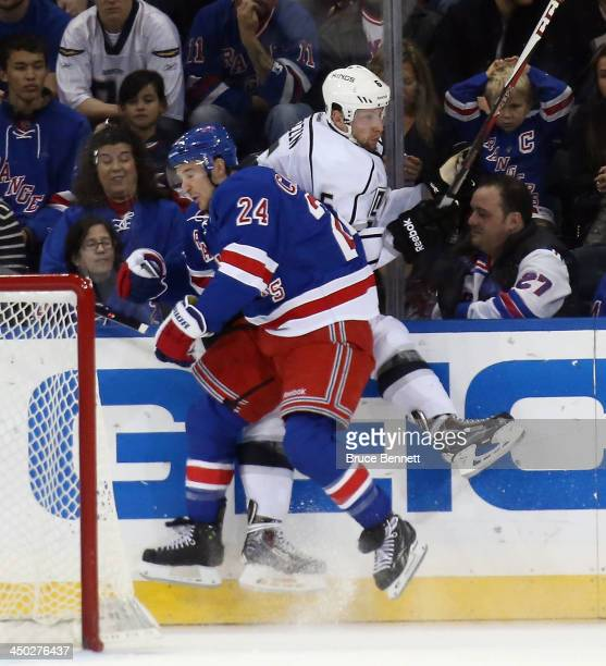 Ryan Callahan of the New York Rangers hits Jake Muzzin of the Los Angeles Kings against the boards during the first period at Madison Square Garden...