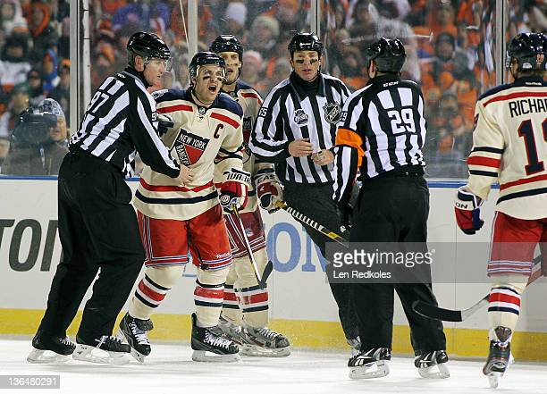 Ryan Callahan of the New York Rangers is restrained by Linesmen Jean Morin and Pierre Racicot as he argues a call with Referee Ian Walsh against the...