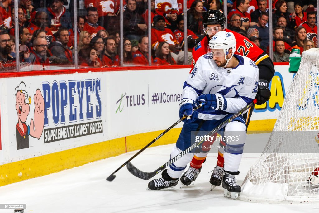 Ryan Callahan #24 of the Tampa Bay Lightning and Travis Hamonic #24 of the Calgary Flames go after the puck in an NHL game on February 1, 2018 at the Scotiabank Saddledome in Calgary, Alberta, Canada.