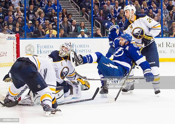 Ryan Callahan of the Tampa Bay Lightning is checked by Tyson Strachan and his skate hits goalie Jhonas Enroth of the Buffalo Sabres in the mask...