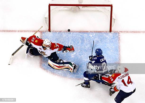 Ryan Callahan of the Tampa Bay Lightning scores a goal against goalie Dan Ellis of the Florida Panthers during the second period at the Tampa Bay...