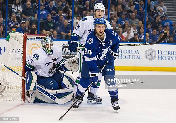 Ryan Callahan of the Tampa Bay Lightning skates against goalie Jacob Markstrom and Ben Hutton of the Vancouver Canucks during the third period at the...