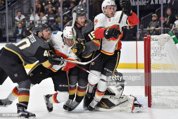 Ryan Carpenter and Jon Merrill of the Vegas Golden Knights skate to the puck against Micheal Ferland and Mark Jankowski of the Calgary Flames during...