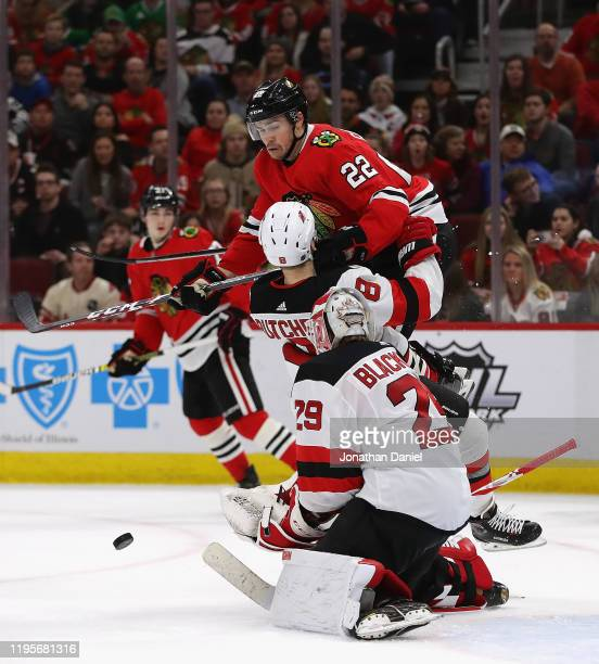 Ryan Carpenter of the Chicago Blackhawks leaps on top of Will Butcher of the New Jersey Devils as a puck is shot at Mackenzie Blackwood at the United...