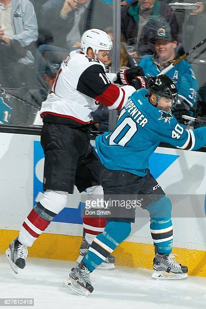 Ryan Carpenter of the San Jose Sharks is checked by Martin Hanzal of the Arizona Coyotes during a NHL game at SAP Center at San Jose on November 29,...