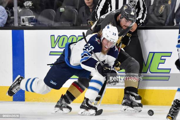 Ryan Carpenter of the Vegas Golden Knights and Patrik Laine of the Winnipeg Jets skate to the puck in Game Three of the Western Conference Final...