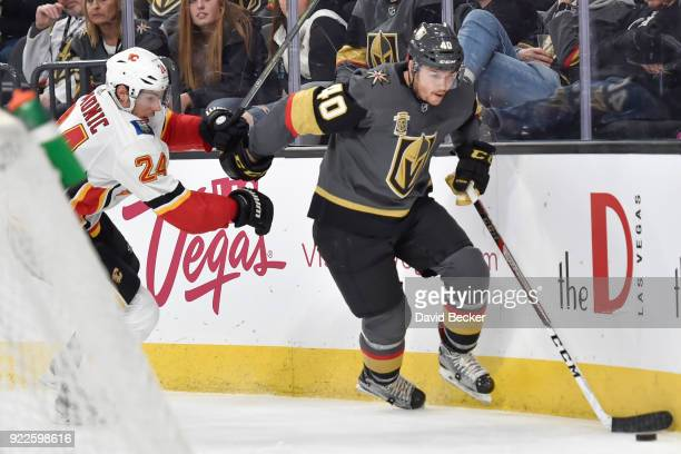Ryan Carpenter of the Vegas Golden Knights skates with the puck while Travis Hamonic of the Calgary Flames defends during the game at TMobile Arena...