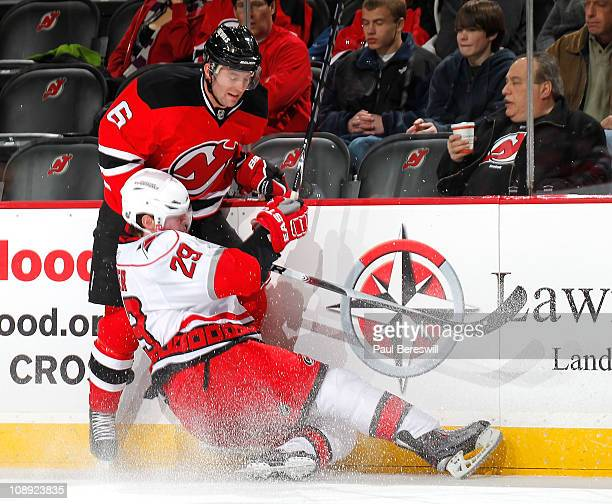 Ryan Carter of the Carolina Hurricanes goes down as he checked Andy Greene of the New Jersey Devils during the first period of an NHL hockey game at...