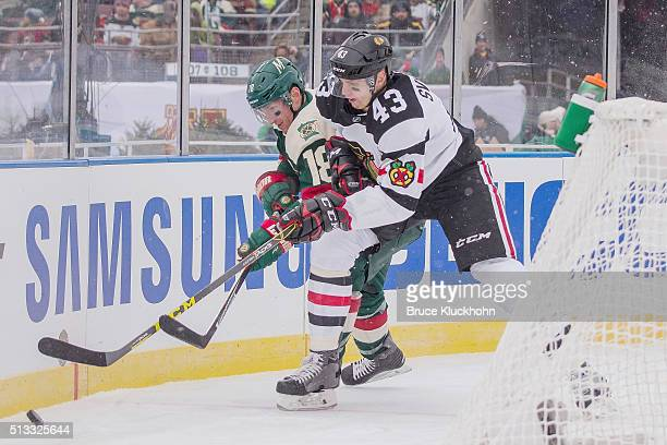 Ryan Carter of the Minnesota Wild and Viktor Svedberg of the Chicago Blackhawks battle for the puck during the 2016 Coors Light NHL Stadium Series on...