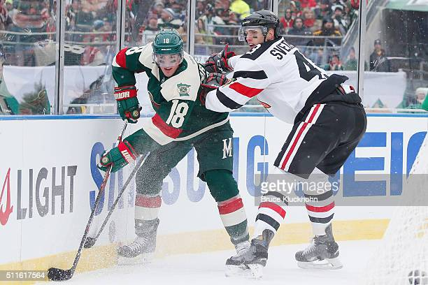 Ryan Carter of the Minnesota Wild controls the puck along the boards with Viktor Svedberg of the Chicago Blackhawks defending during the 2016 Coors...