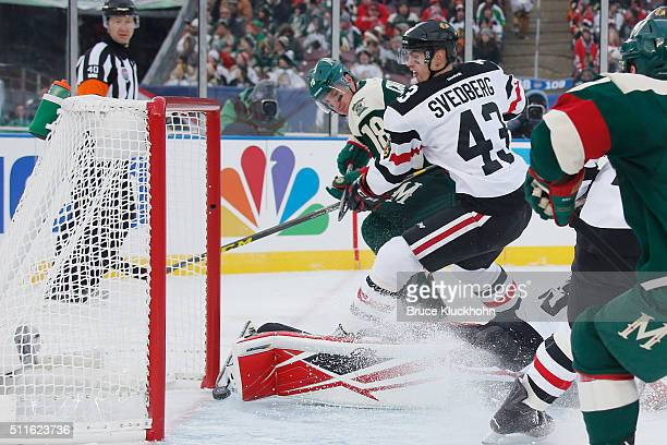 Ryan Carter of the Minnesota Wild scores a goal with Viktor Svedberg of the Chicago Blackhawks defending during the 2016 Coors Light NHL Stadium...