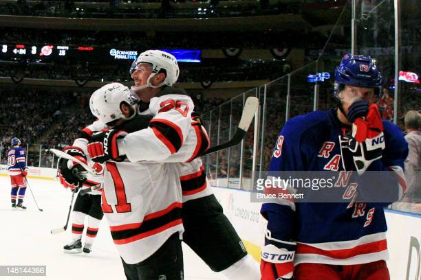 Ryan Carter of the New Jersey Devils celebrates his third period goal with Stephen Gionta as Brad Richards of the New York Rangers reacts in Game...