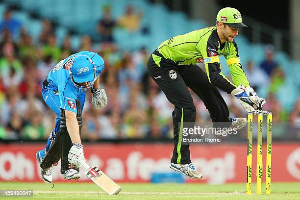 Ryan Carters of the Thunder attempts to run out Michael Klinger of the Strikers during the Big Bash League match between Sydney Thunder and the...