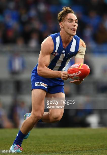 Ryan Clarke of the Kangaroos handballs during the round 19 AFL match between the North Melbourne Kangaroos and the Melbourne Demons at Blundstone...