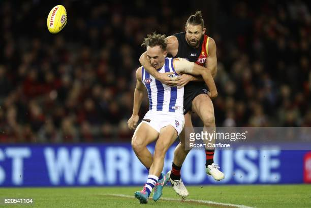 Ryan Clarke of the Kangaroos is challenged by Cale Hooker of the Bombers during the round 18 AFL match between the Essendon Bombers and the North...
