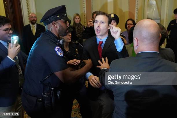 Ryan Clayton of Americans Take Action is corralled by police after he threw paper Russian flags at Senate Majority Leader Mitch McConnell and US...